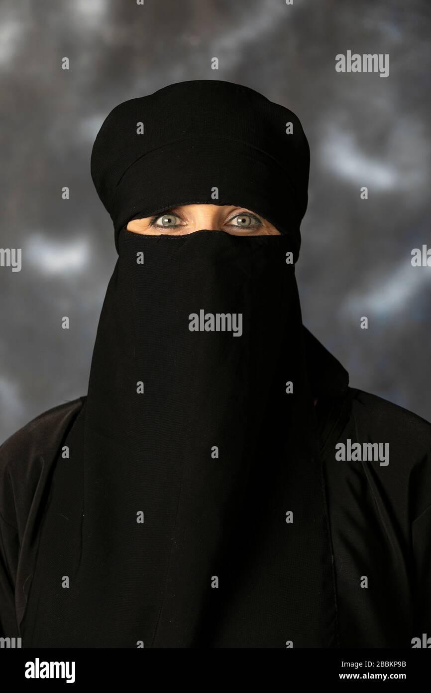 Porträt einer muslimischen Frau mit überdachtem Gesicht. Die Fotosession fand im Studio auf dunklem Hintergrund statt. Ein wunderschönes, junges 50-jähriges Mädchen. Stockfoto