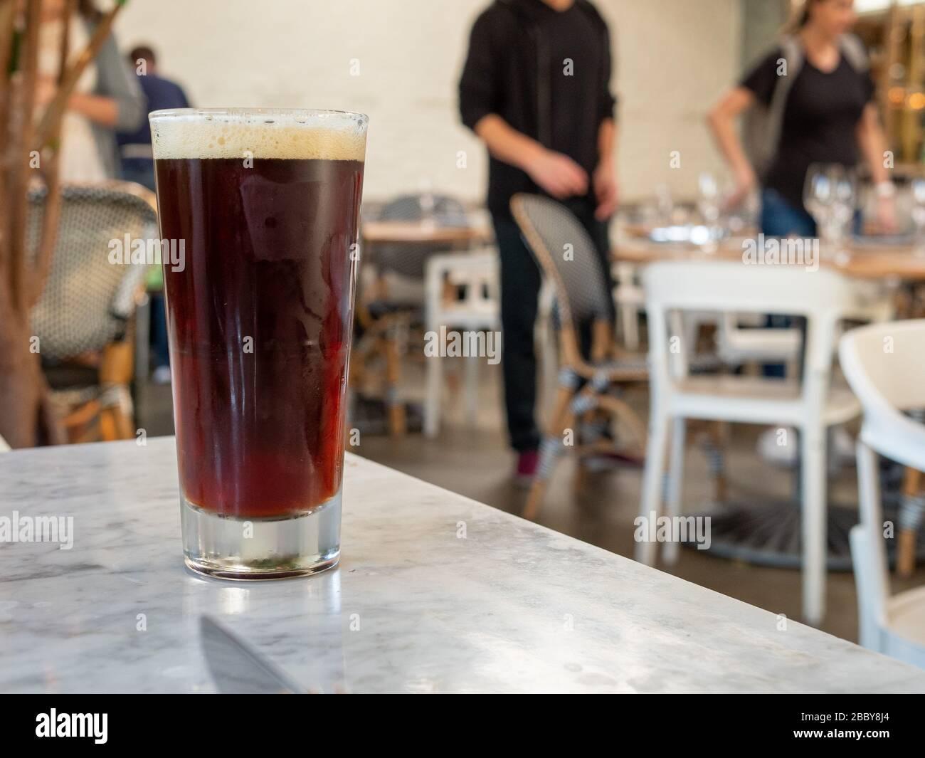 Dunkles Bier, das auf dem Tisch im Restaurant sitzt, und die Gäste sitzen Stockfoto