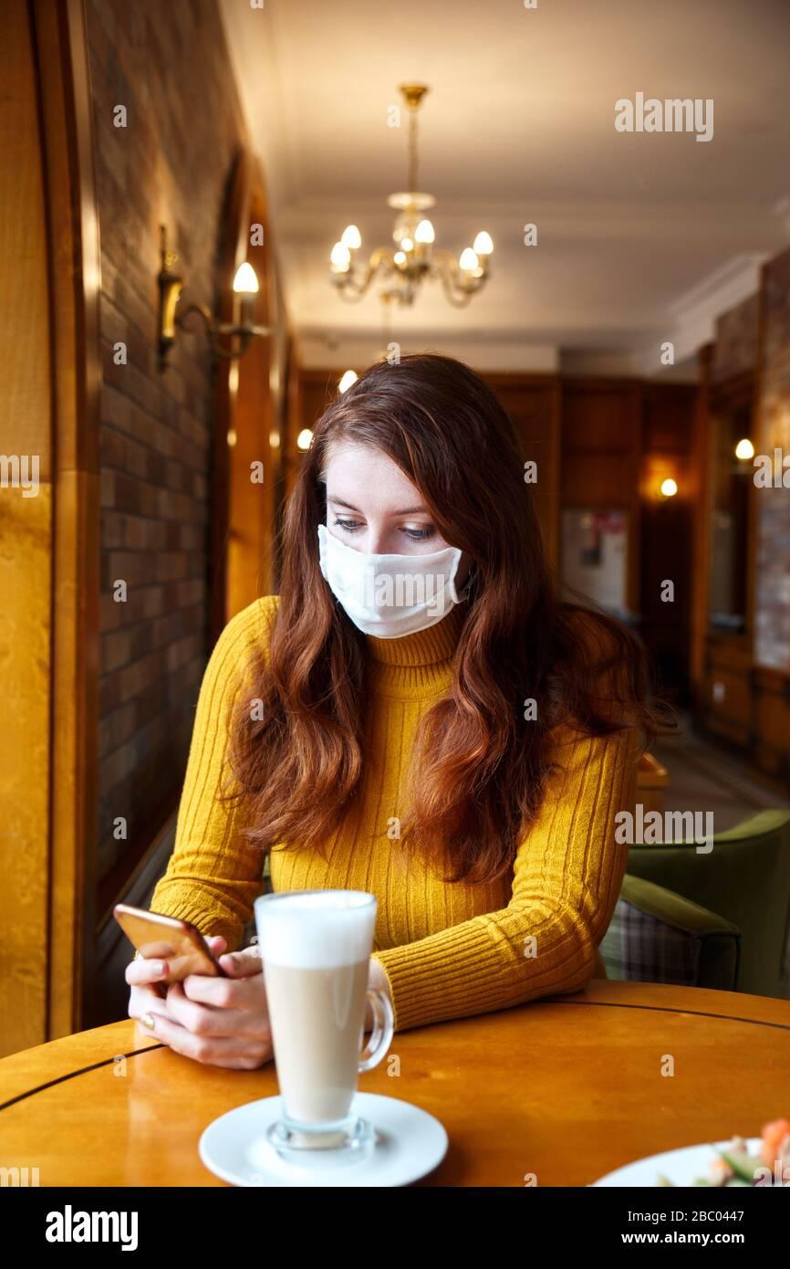Junge kaukasische Frau, die Gesichtsschutzmaske trägt und Nachrichten auf ihrem Handy in der Halle liest. Stockfoto