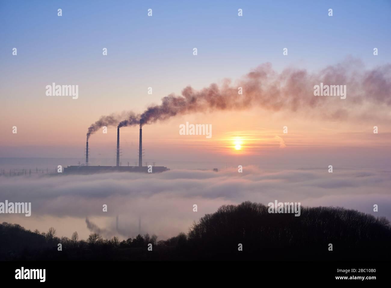 Horizontaler Schnappschuss von drei Raucherstapeln des Wärmekraftwerks am Horizont, die vom Hügel aufgenommen wurden, Rohre befinden sich im Abendnebel am blauen Himmel, Kopierraum. Umweltverschmutzung Stockfoto
