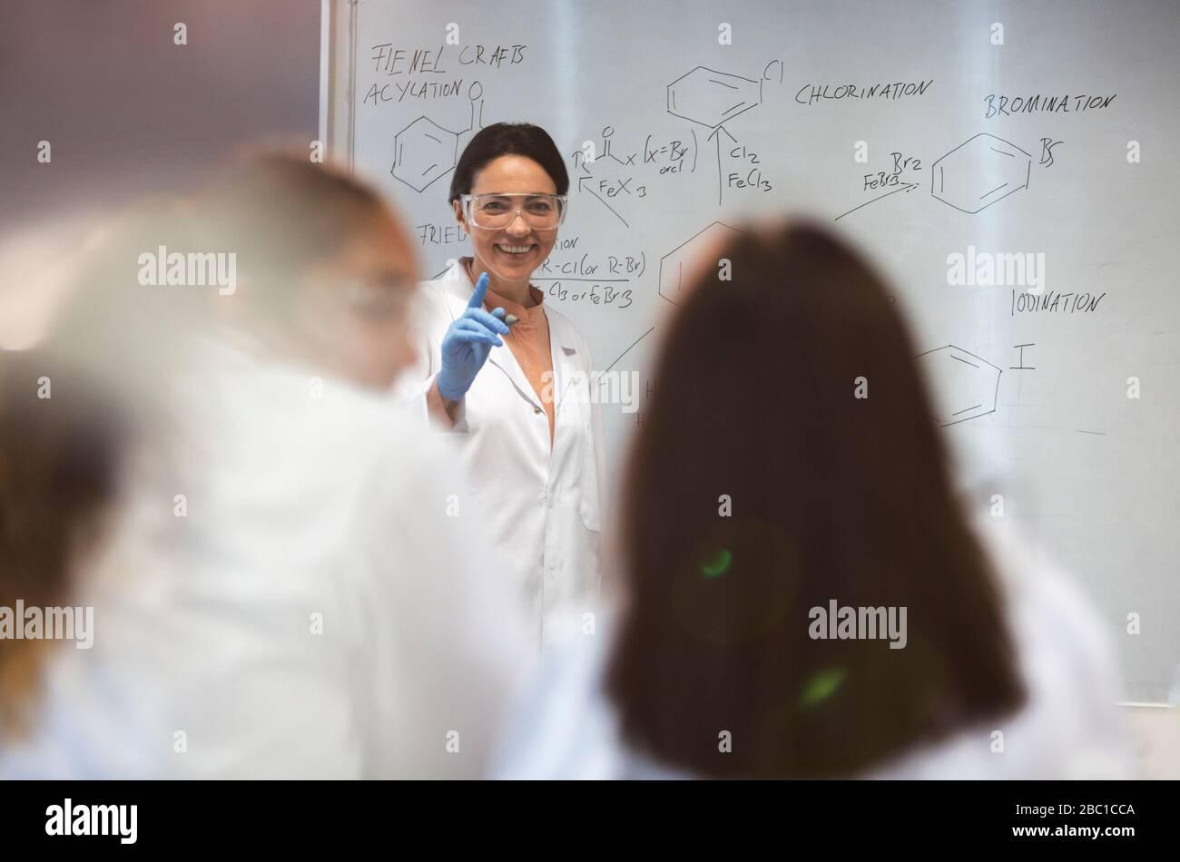 Lächelnde wissenschaftliche Lehrerin, die am Whiteboard im Klassenzimmer Unterricht führt Stockfoto