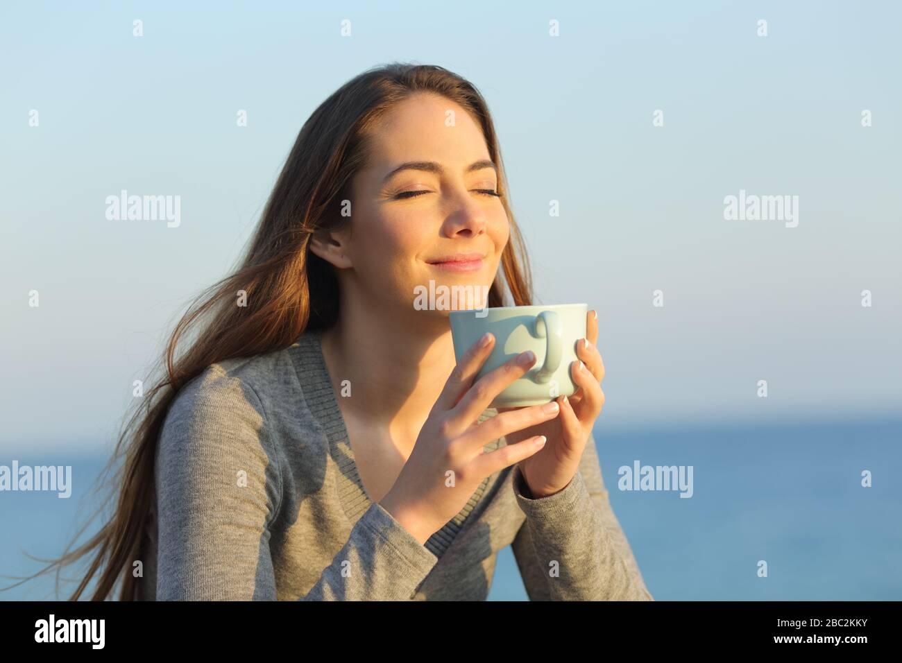 Zufriedene Frau mit geschlossenen Augen, die Kaffee bei Sonnenuntergang am Strand trinkt Stockfoto