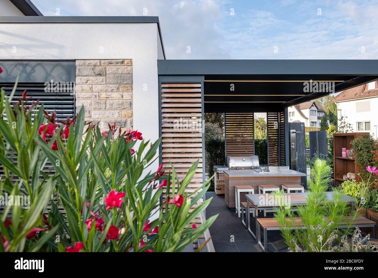 Moderne überdachte Terrasse mit Außenküche, Sitzecke und Kamin mit ...