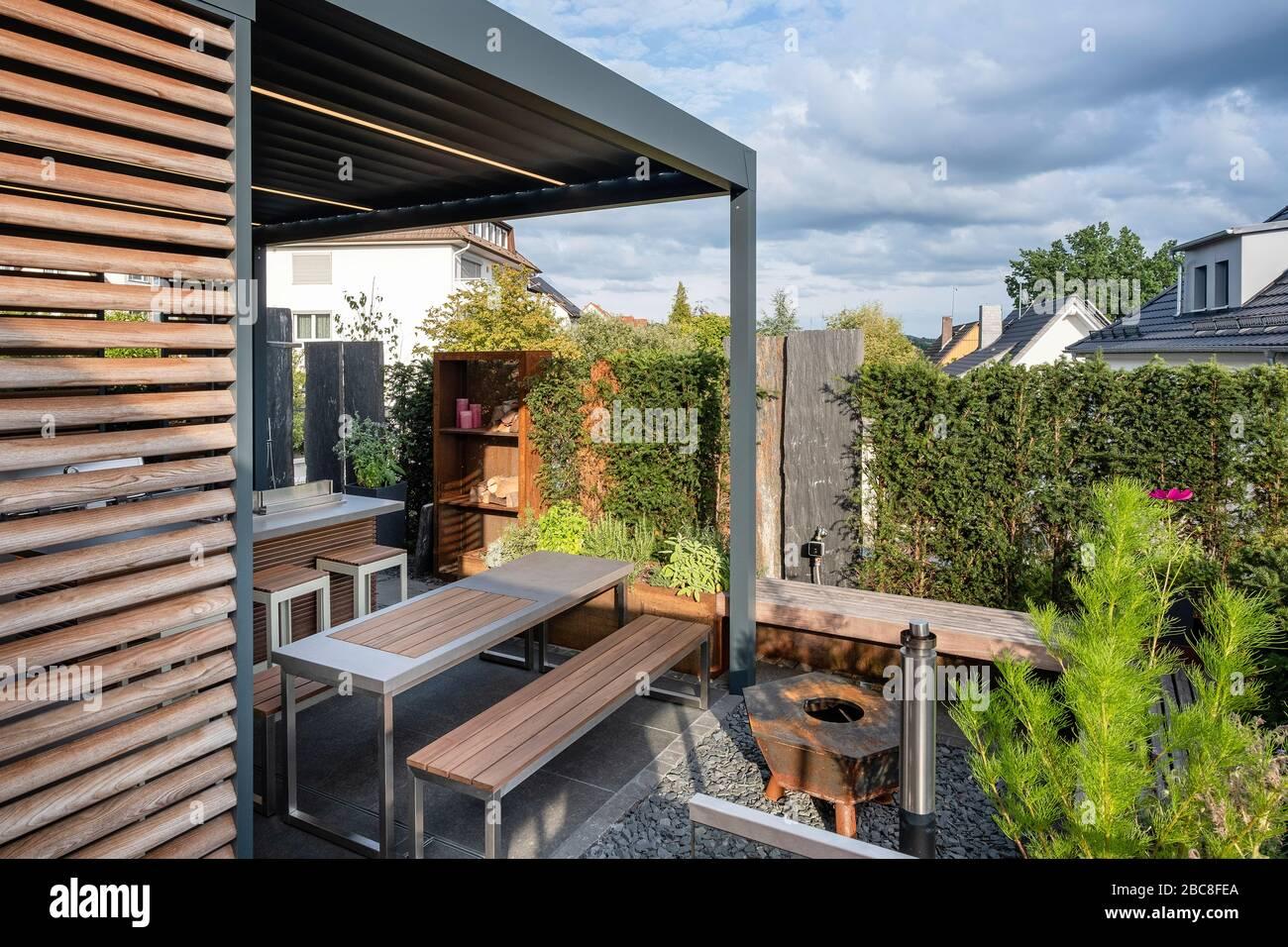 Moderne überdachte Terrasse mit Sitzgelegenheiten und Kamin ...