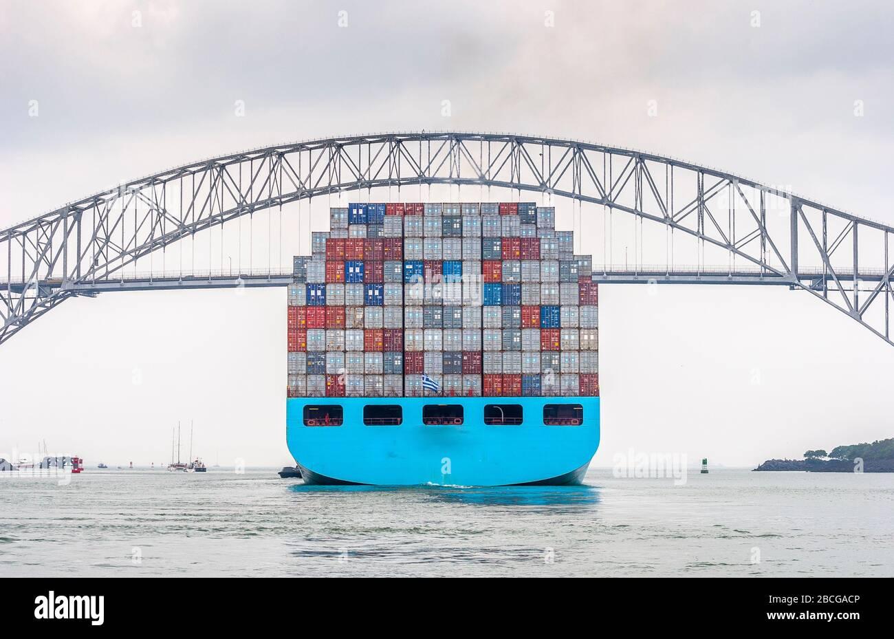 Containerschiff verlässt den Panamakanal und passiert die Brücke von Amerika, die einzige Straßenverbindung zwischen Nord- und Südamerika Stockfoto