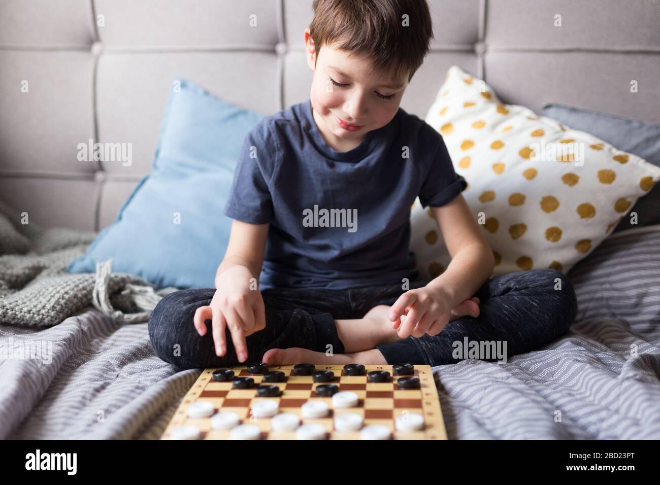 Junge Kinder spielen mit den Schachspielen ein Tischspiel im Bett. Bleiben Sie zu Hause Quarantänekonzept. Freizeitkonzept für Brettspiele und Kinder. Familienzeit. Stockfoto