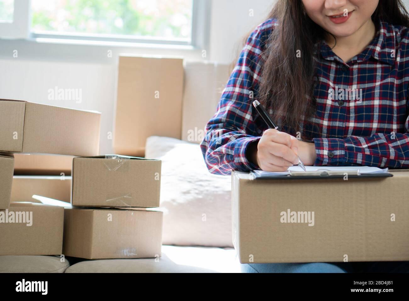 Junge Frau Unternehmer, auf dem Sofa sitzen und arbeiten zu Hause. Die Aufnahme der Jahresumsatz und die Planung auf Strumpf Produkte zur Lieferung Versand onl Stockfoto