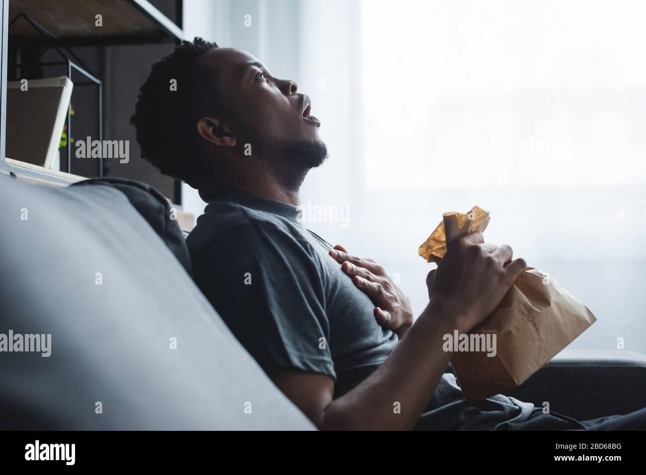 Schockierter afroamerikanischer Mann, der Papiertüte hält, während er zu Hause Panikattacken hatte Stockfoto
