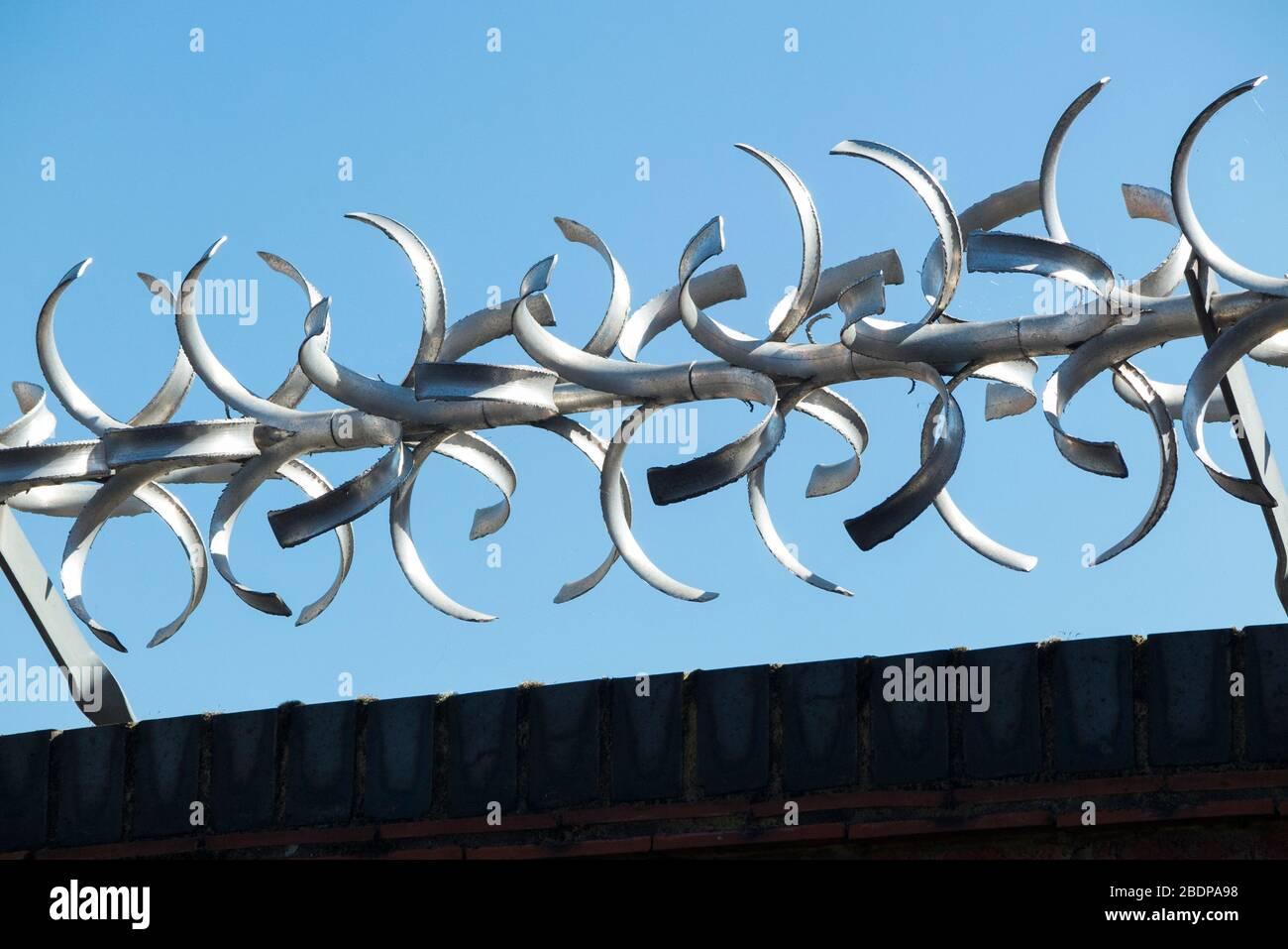 Hohe und hohe Ziegelwand mit moderner drehbarer Sicherheitsbarriere mit gebogenen Stachelschwanen/Rasiermesserkanten auf der Oberseite, für Sicherheitszwecke. (116) Stockfoto