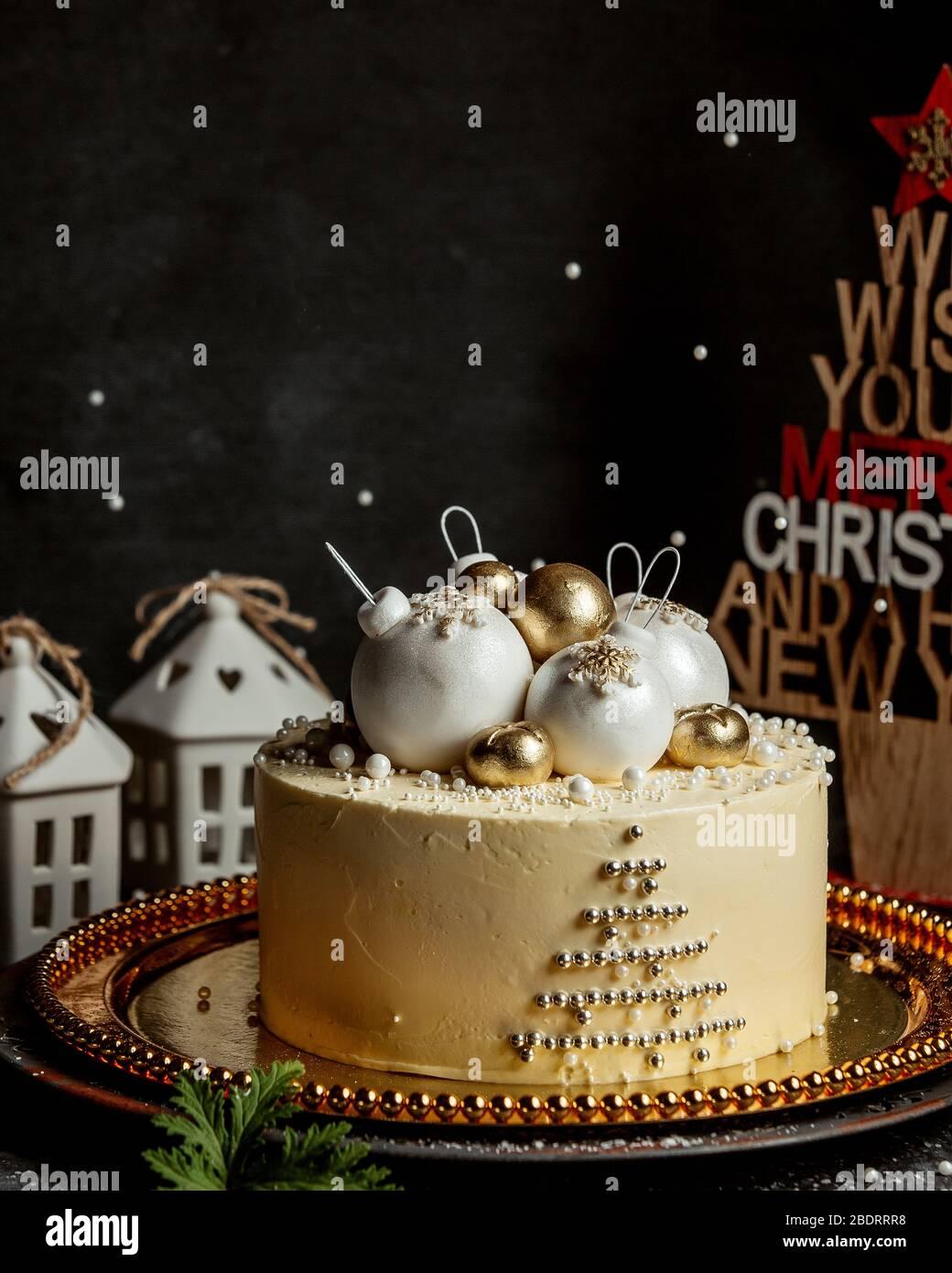 weihnachtskuchen mit Weihnachtsbaum Spielzeug in Gold und weiß gekrönt Stockfoto