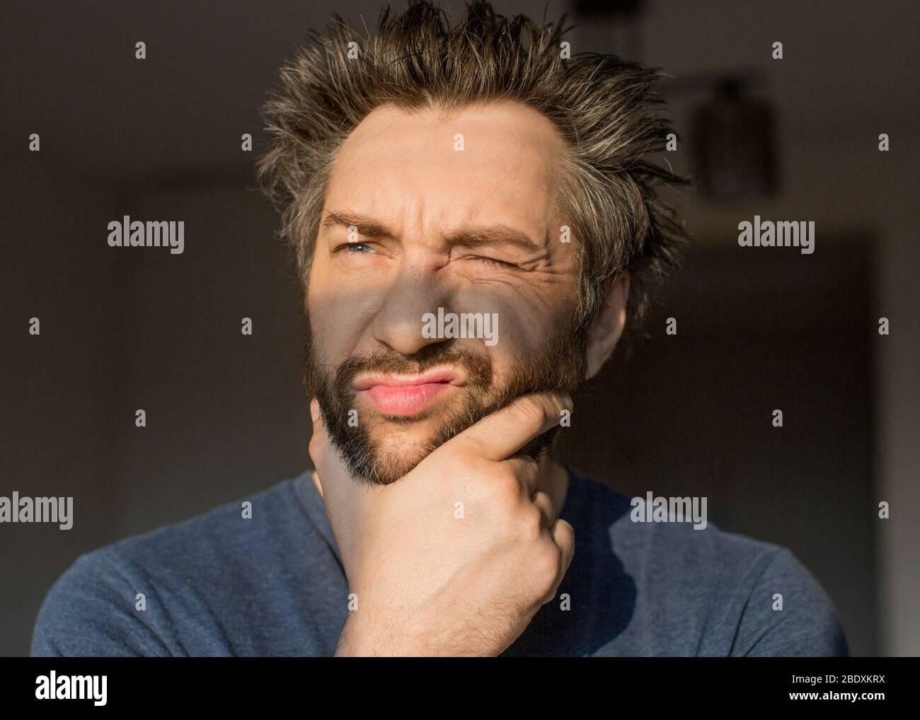 Lustiger Mann nach dem Aufwachen kratzt seinen Bart, Blick auf die Morgensonne. Hochformat schließen. Stockfoto