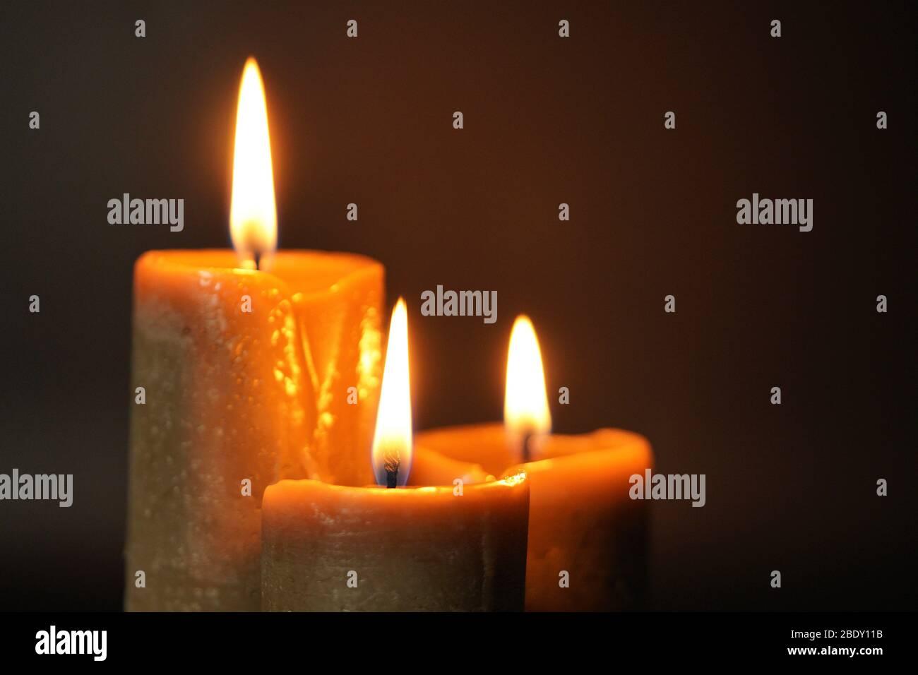 Gruppe von drei braunen brennenden Kerzen auf schwarzem Hintergrund Nahaufnahme. Konzept des Komforts, der Romantik, des Mystikers, des Okkultismus, der Religion, des Symbols der Erinnerung Stockfoto