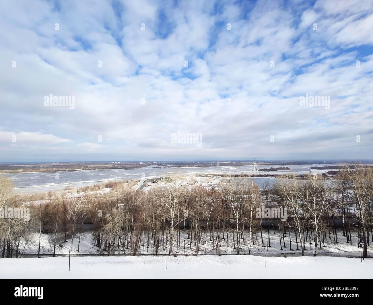 Schöne Flusslandschaft im frühen Frühling. Weiße Wolken über dem Fluss und Bäume an einem sonnigen Tag nach dem Schneeschmelzen. Stockfoto