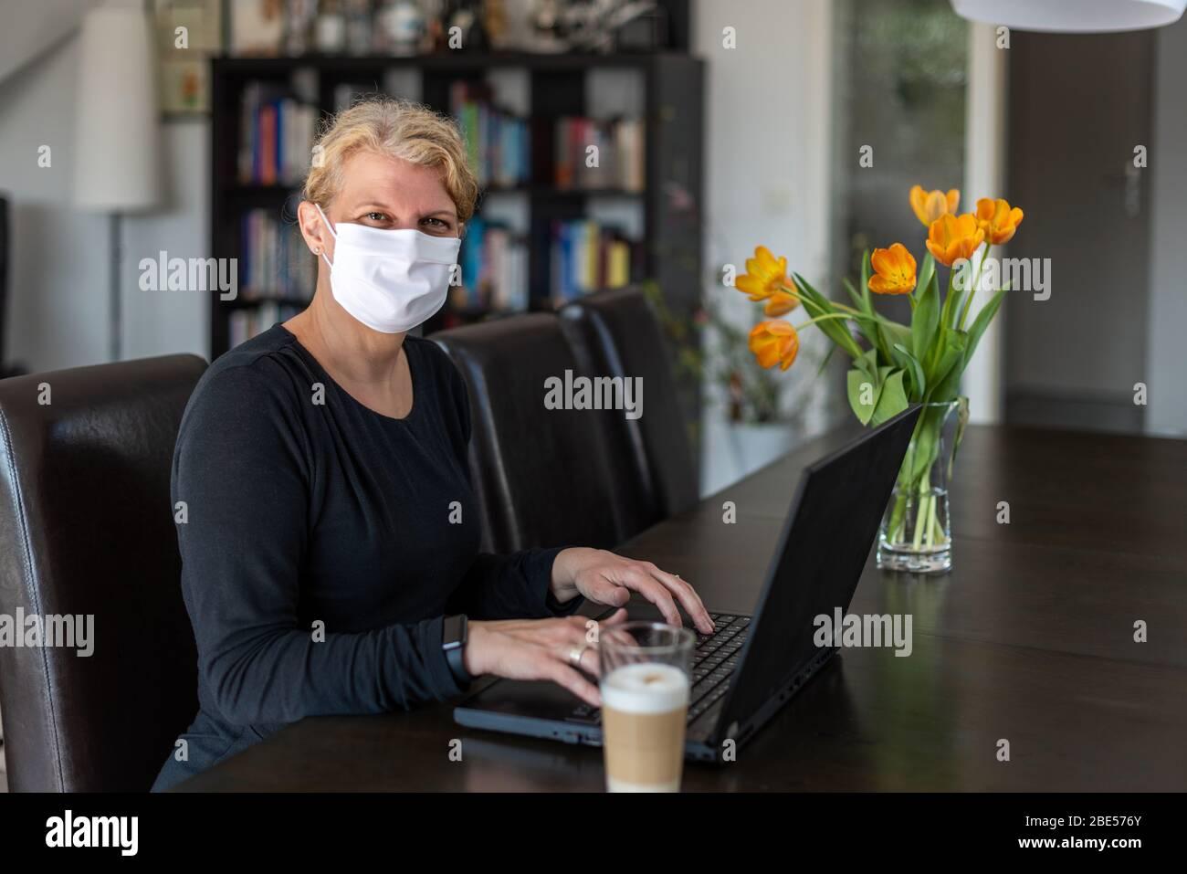 Kaukasierin mittleren Alters arbeitet von zu Hause aus auf einem Laptop in ihrem Wohnzimmer, trägt Gesichtsschutzmaske, während in Quarantäne und Isolation Stockfoto