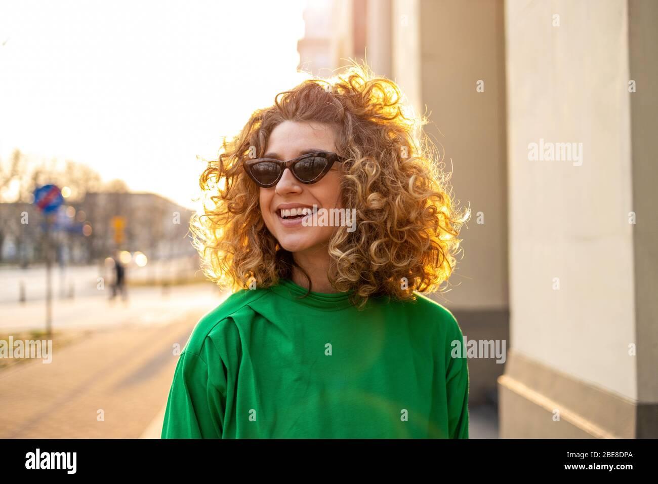 Porträt einer jungen Frau mit lockigen Haaren in der Stadt Stockfoto