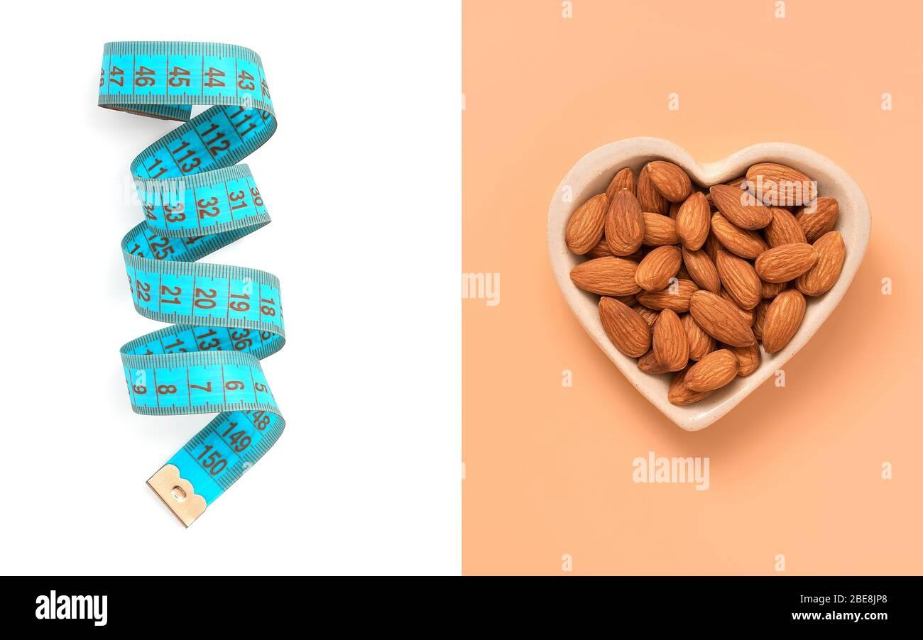 Kreatives Layout aus blauem Zentimeter-Band auf weißem Hintergrund und Mandelnuss in einer Herzschale auf einem pastellrosa Hintergrund. Das Konzept der Ernährung und weig Stockfoto