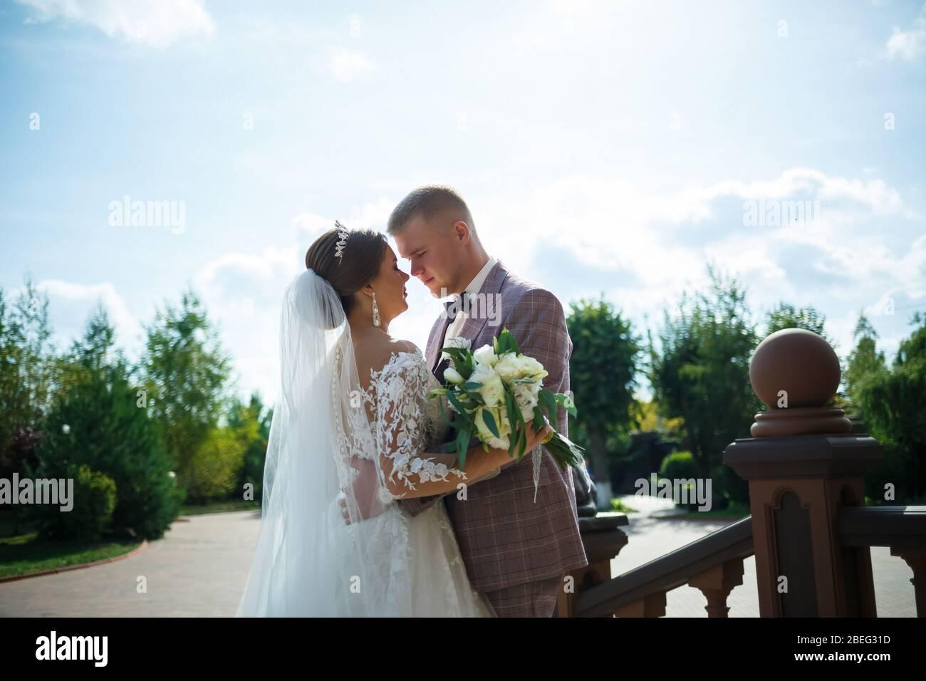 Braut im weißen Kleid und Bräutigam in Kostüm kuscheln und spazieren im Park Stockfoto