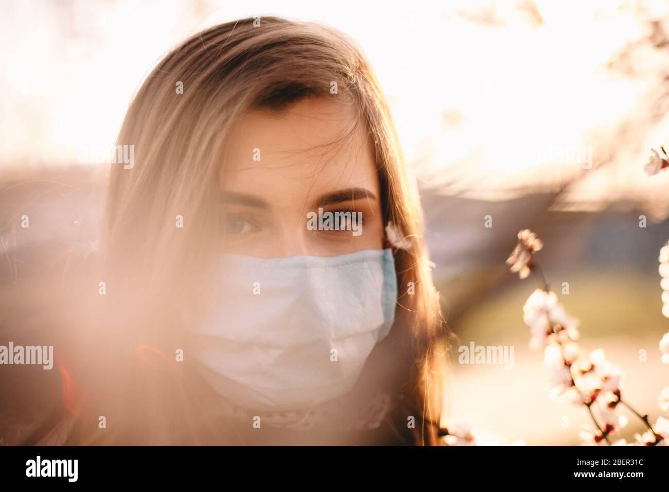 Nahaufnahme Porträt von Teenager-Mädchen mit Gesicht medizinische Maske stehend von blühenden Baum im Frühjahr Stockfoto
