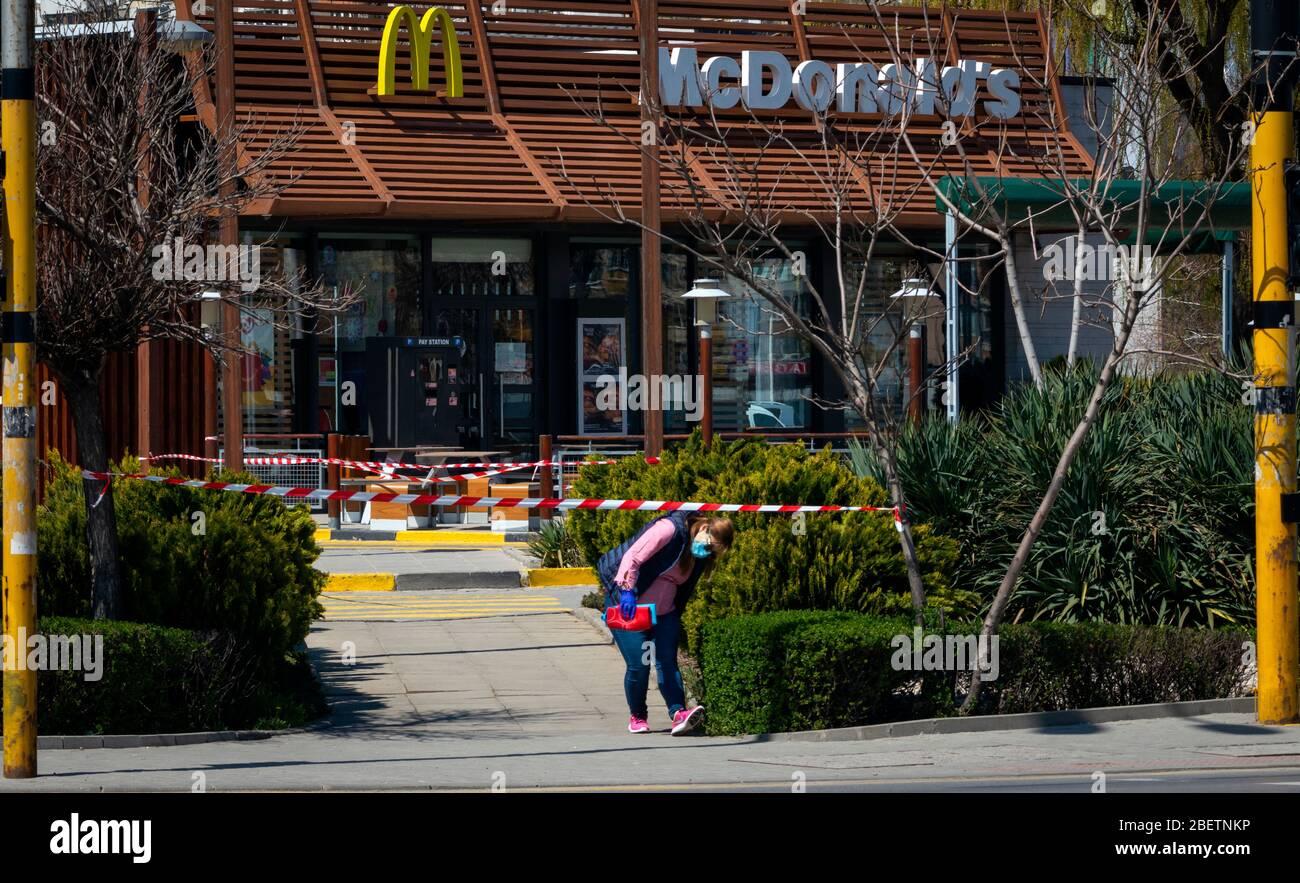 Frau mit Schutzmaske vor dem geschlossenen für normale Geschäfte McDonald's Fast-Food-Restaurant erlaubt nur Drive-in oder Drive-Thru Essen zum Mitnehmen aufgrund der Ausbreitung der Coronavirus Pandemie von Covid-19 in Sofia, Bulgarien. Kredit: Ognyan Trifonov / Alamy Stockfoto