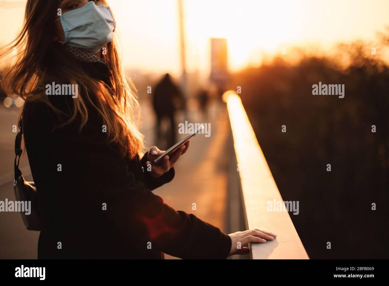 Junge Frau mit Schutzmaske Gesicht medizinische Maske mit Smartphone während das Geländer auf der Brücke in der Stadt bei Sonnenuntergang stehen Stockfoto