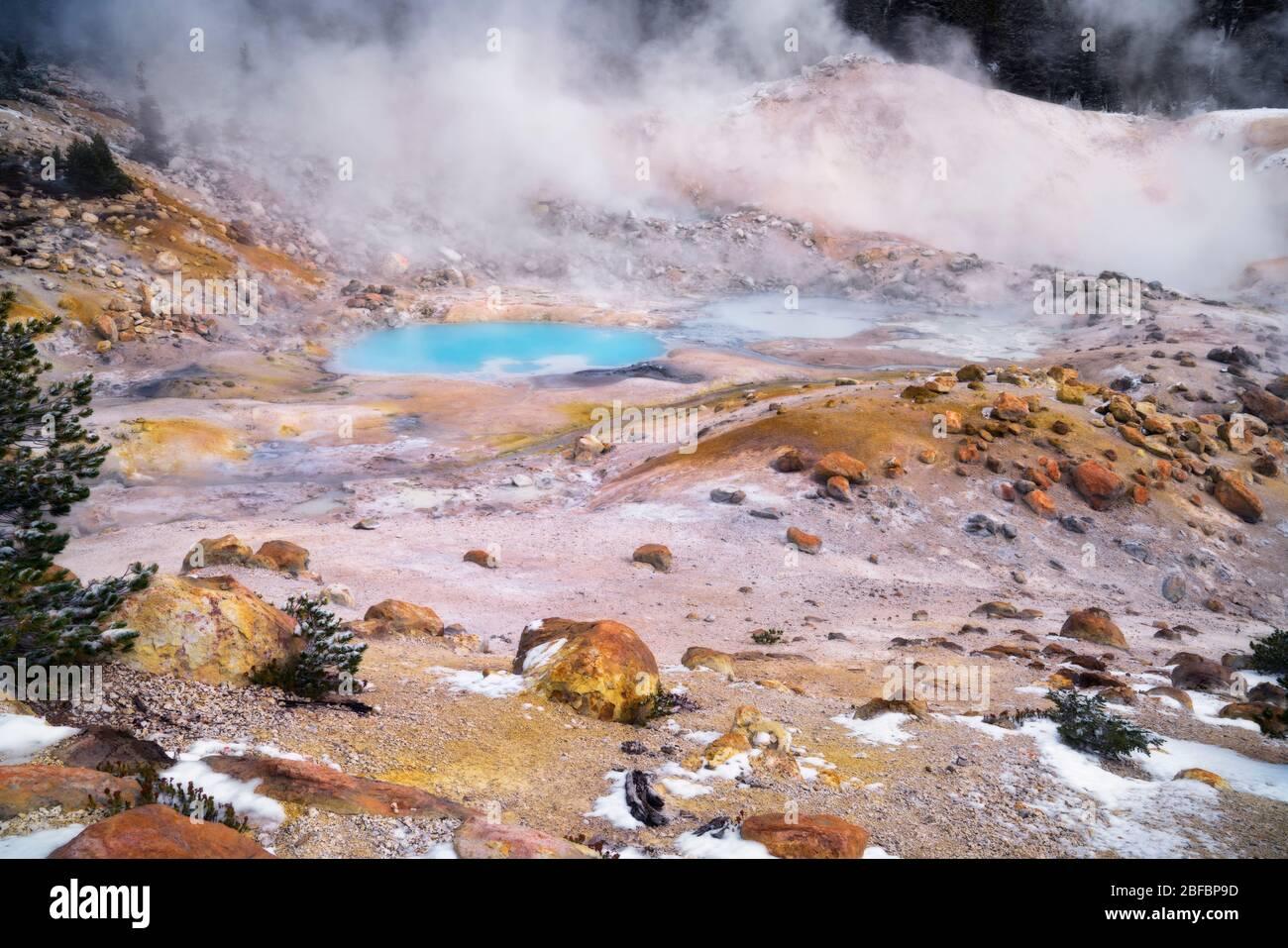 Dampf steigt aus dem türkisfarbenen Pool und den vielen geothermischen Eigenschaften, die in der Bumpass Hell im kalifornischen Lassen Volcanic National Park zu finden sind. Stockfoto