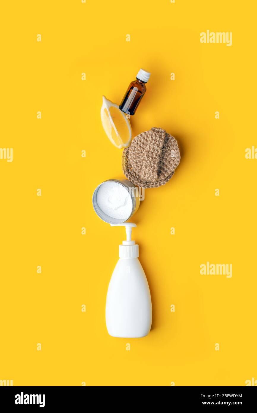 Kreatives Konzept umweltfreundlicher natürlicher Reinigungsmittel auf gelbem Küchentisch: Soda, ätherische Öle, Zellulose-Schwamm, Lumpen, Zitrone, Seife, Essig Stockfoto