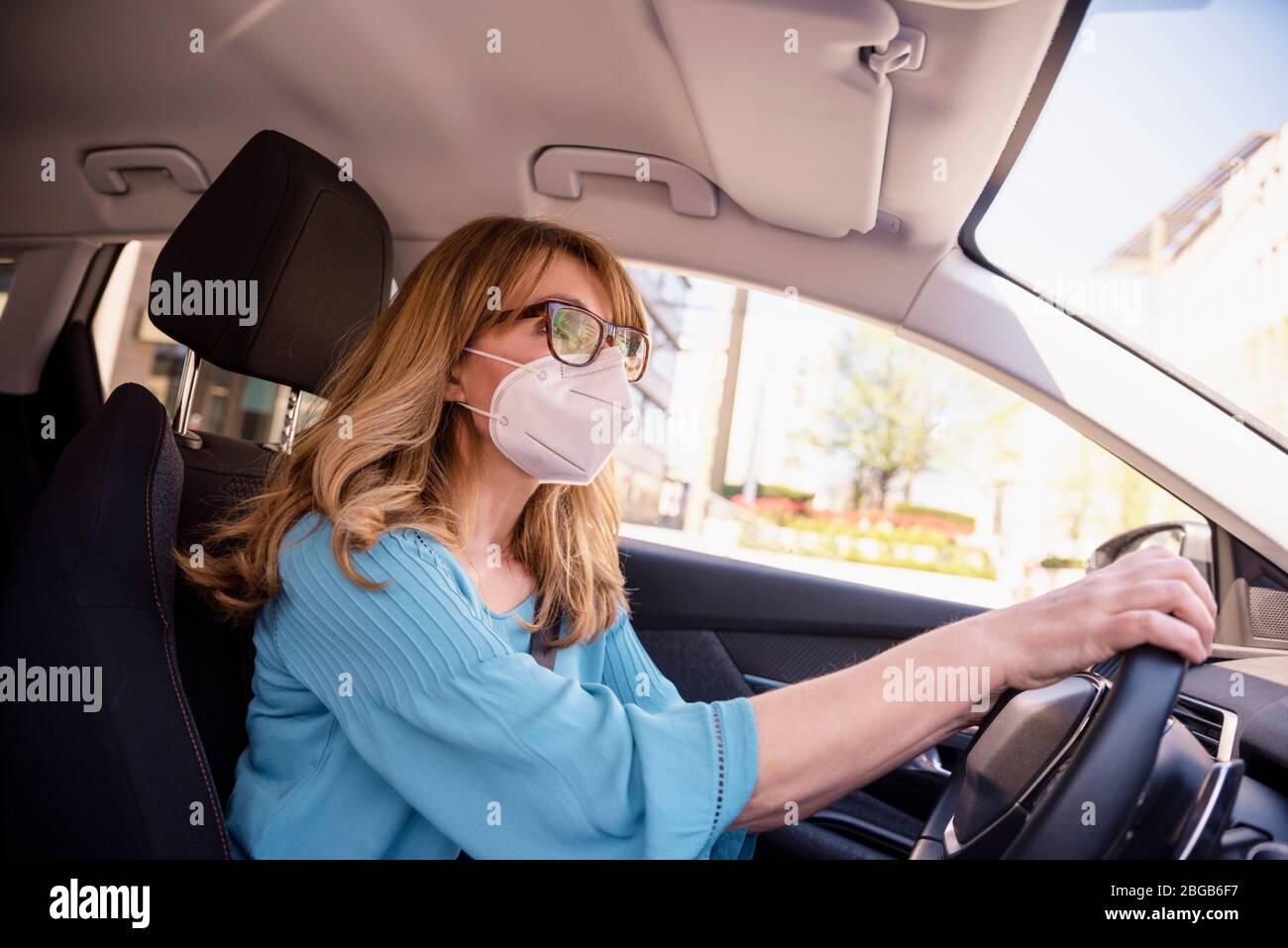 Aufnahme einer Frau mittleren Alters, die während der Coronavirus-Pandemie mit dem Auto eine Gesichtsmaske trägt. Stockfoto