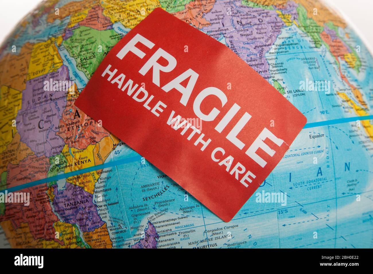 Eine Erdkugel mit einer zerbrechlichen Hand mit Pflegeaufkleber Stockfoto