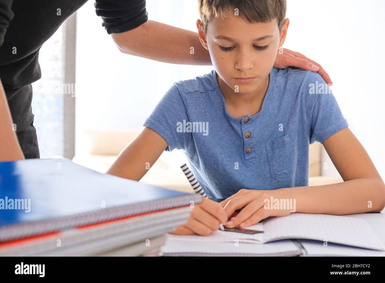 Kind sitzt am Tisch mit vielen Büchern Notizbücher und Hausaufgaben zu machen. Mutter hilft ihm. Lernschwierigkeiten, Lernen zu Hause, Bildung zu Hause Stockfoto