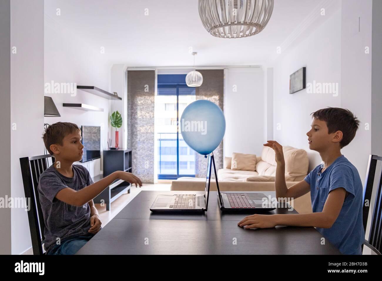 Kinder lernen mit Laptop-Computer und spielen mit Ballon zu Hause. Technologie, Bildung, Online-Fernunterricht für Kinder Stockfoto