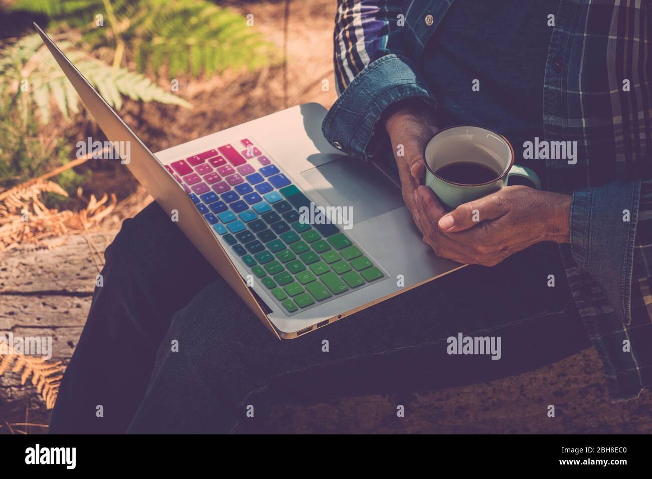 Nahaufnahme Frau im Freien mit Kaffeetasse und Notebook auf den Beinen bereit zu arbeiten und Internet-Verbindung - arbeiten überall ohne Altersbegrenzung für moderne freie Menschen mit Computer und WiFi-Signal Stockfoto