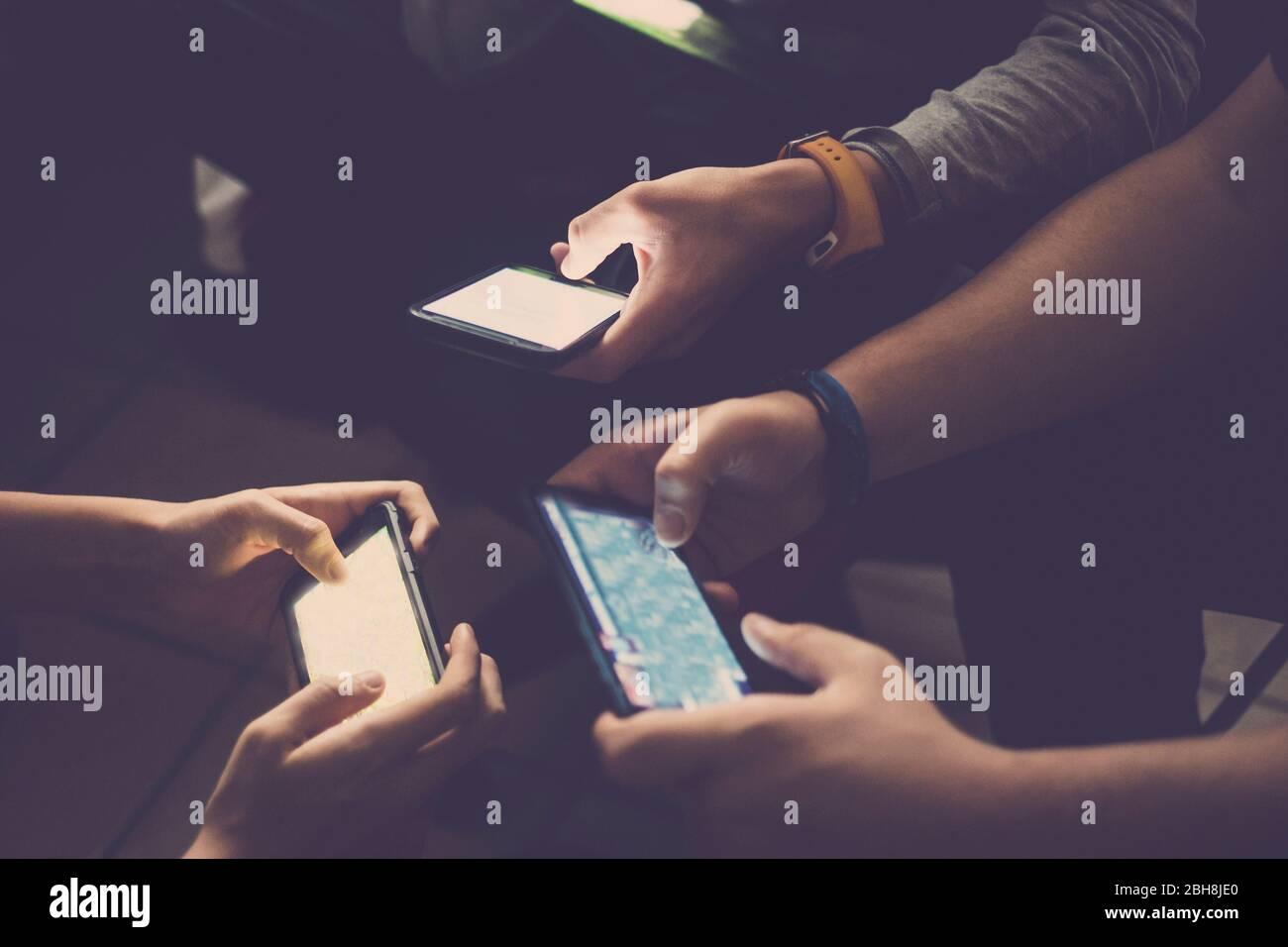 Drei junge kaukasische Teenager Männer spielen alle zusammen mit Handy-Gerät zu Videospielen wie Clan oder Team - übliche Aktivität für Millennial Menschen zu Hause - Technologie-süchtig Menschen Konzept Stockfoto