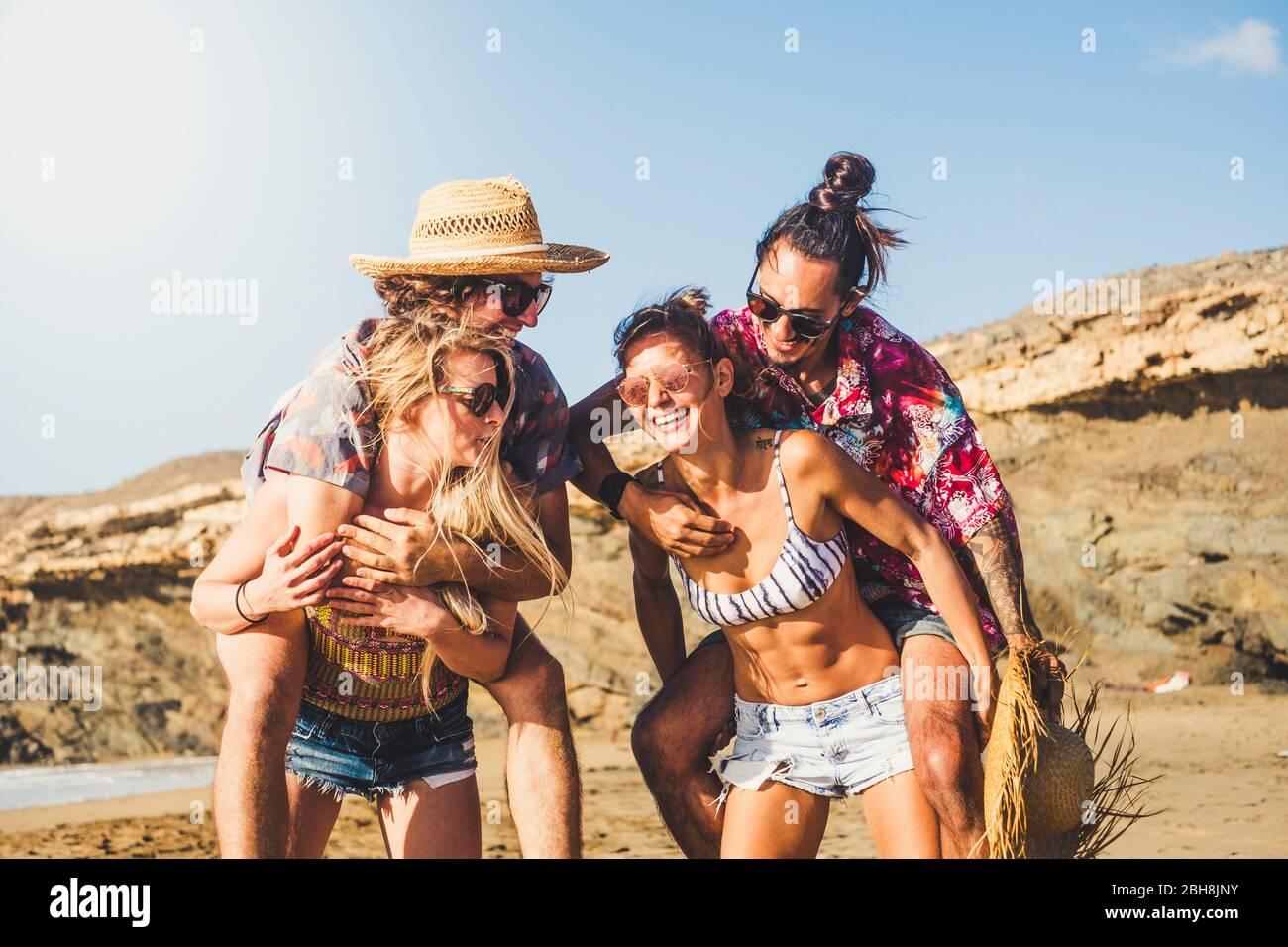 Fröhliche Menschen zwei Paare lachen und haben gemeinsam Spaß - Freunde genießen den Sommerurlaub im berach - Mädchen tragen Jungen - schöne junge Männer und Frauen spielen in glücklicher Freundschaft Stockfoto