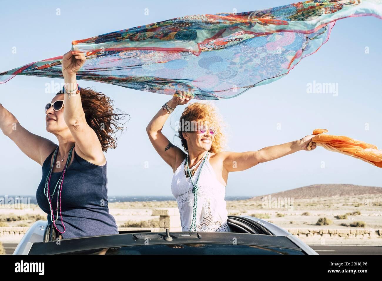 Ein paar Frauen haben Spaß und spielen mit dem Wind, der aus der Spitze eines Cabrios steht und mit dem Wind mit farbigen Pareos spielt - fröhliche Menschen, die unterwegs sind und im Urlaub die Natur genießen Stockfoto