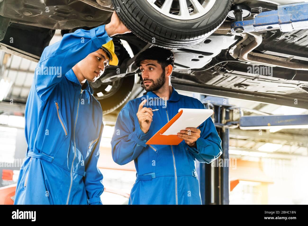 Mechaniker in blauer Arbeitskleidung Uniform inspiziert den Fahrzeugboden mit seinem Assistenten. Auto Reparatur-Service, Berufsberuf Teamwork. Stockfoto