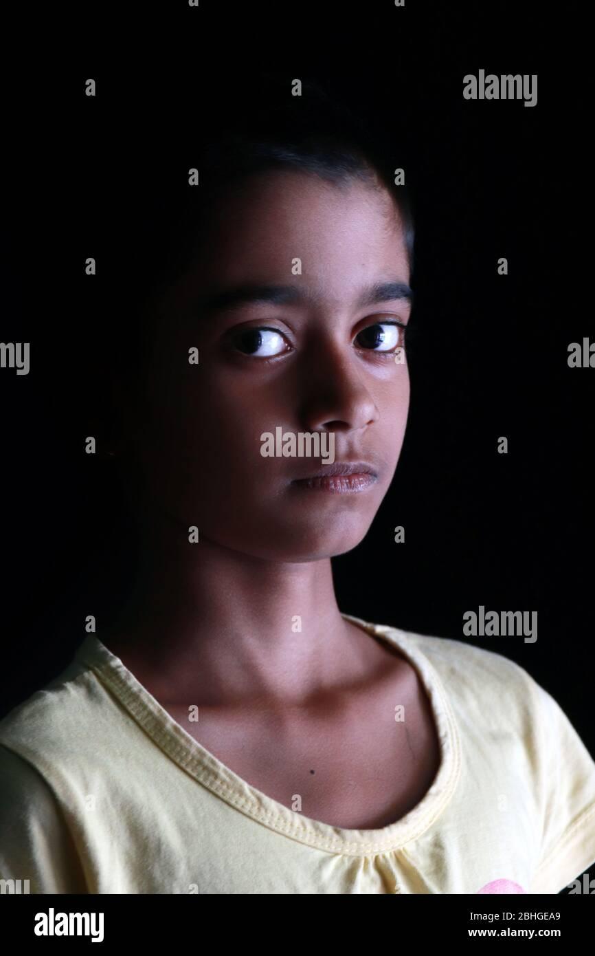 Porträt eines kleinen indischen Mädchens mit kurzen Haaren. Schönes Auge eines Kindes auf schwarzem Hintergrund. Dramatischer Blick eines kleinen Mädchens in Indien. Stockfoto