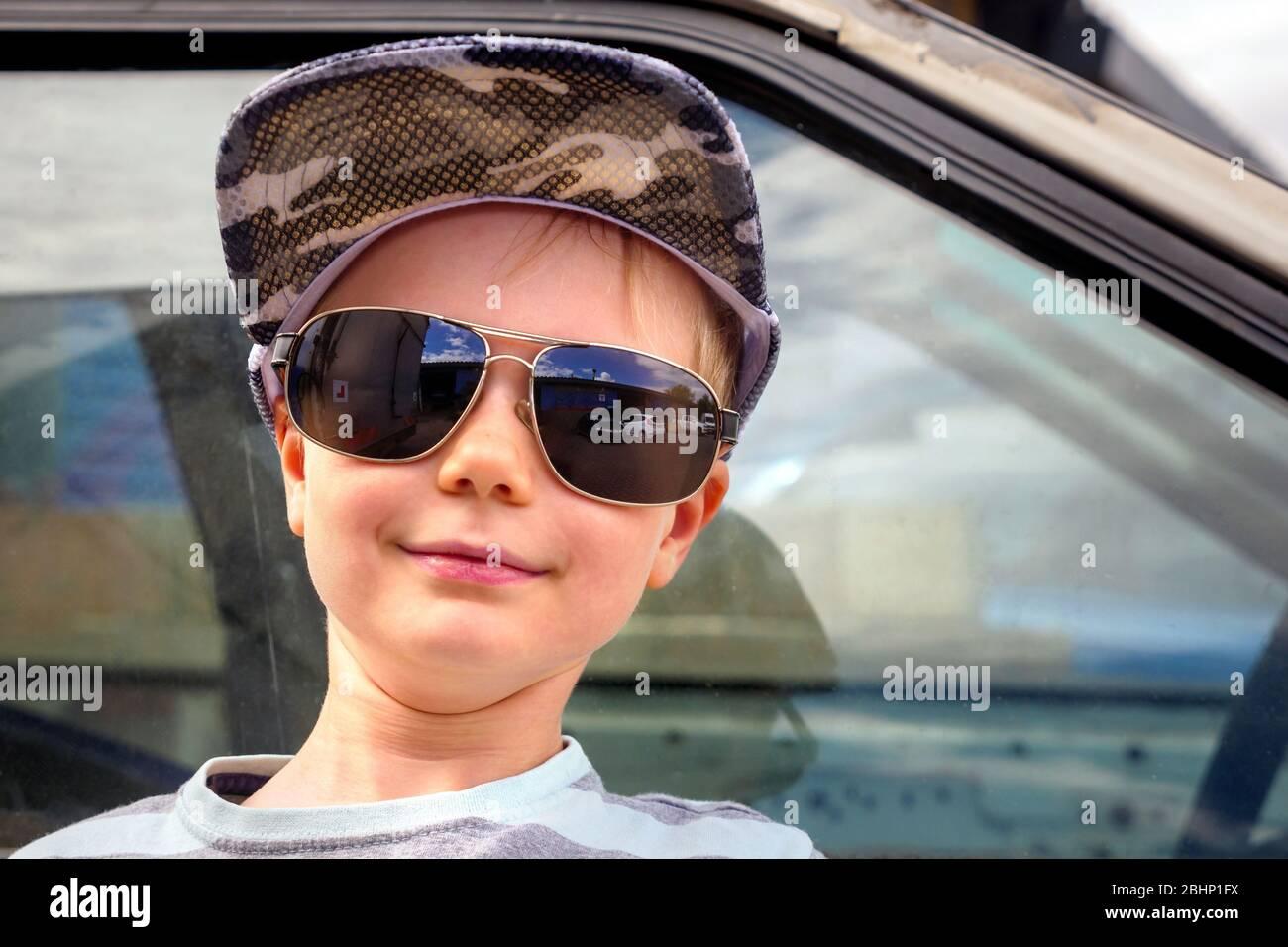 Kleiner Junge Porträt mit Autofenster auf Hintergrund trägt Militärmütze und Väter Brille Stockfoto