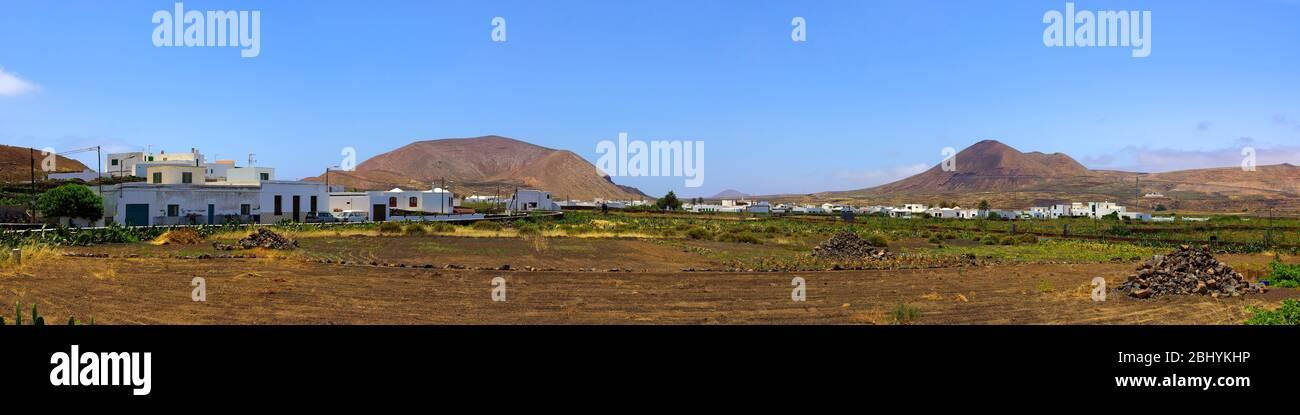Erloschene Vulkankegel und Dörfer mit einstöckiger Architektur in Pueblobauweise prägen das Landschaftsbild auf der kanarischen Insel Lanzarote. Stockfoto