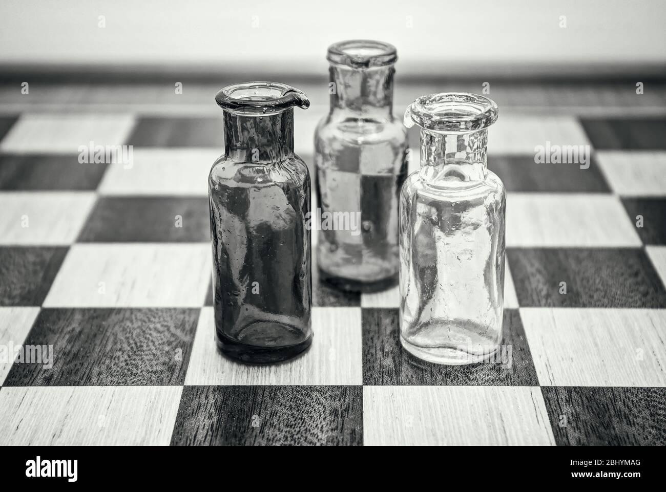 Drei Flaschen im Gespräch auf einem Schachbrett. Stockfoto