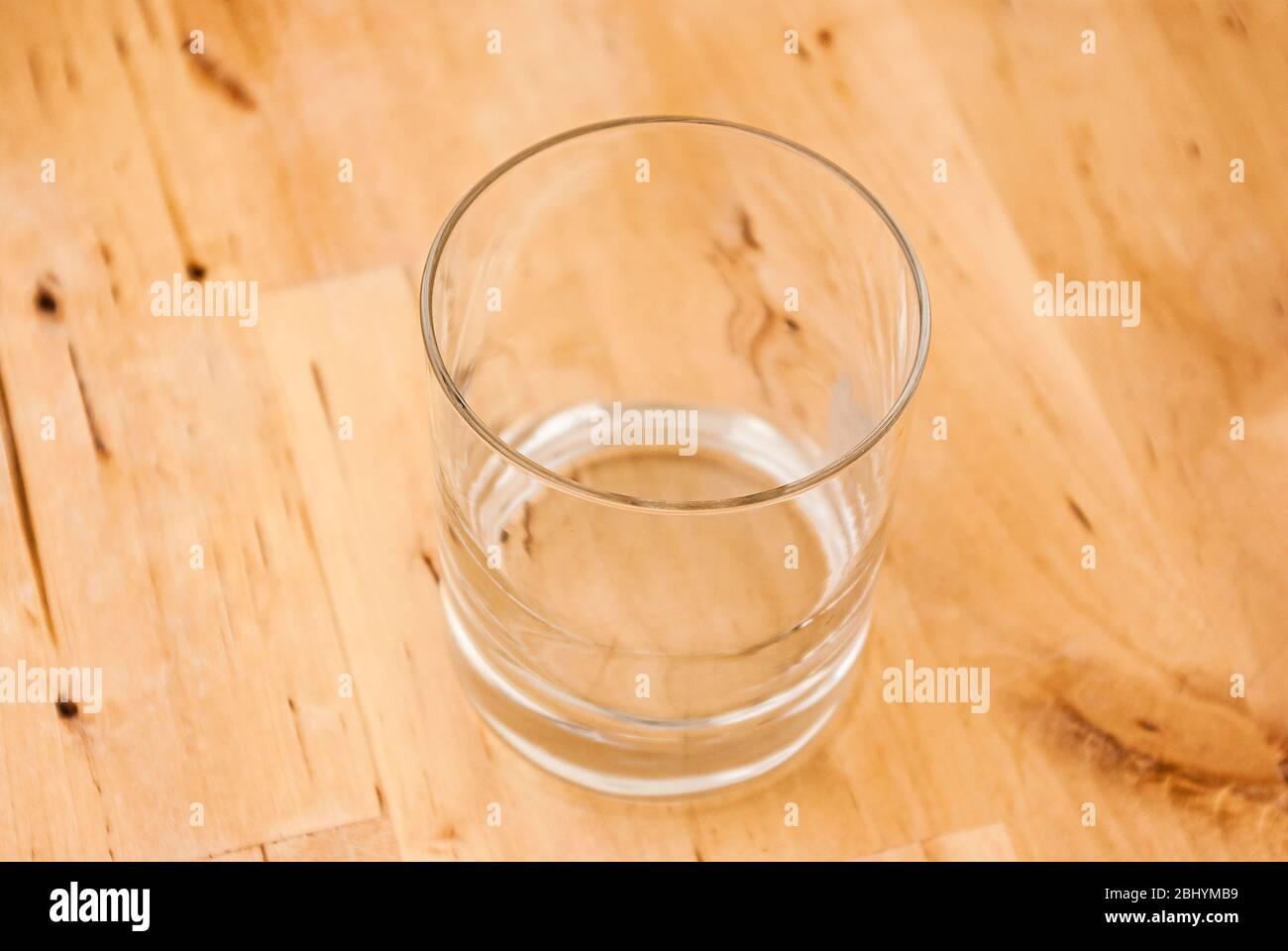 Ein leeres Glas auf einem Holztisch. Einzelnes leeres Glas auf einem Holztisch. Stockfoto