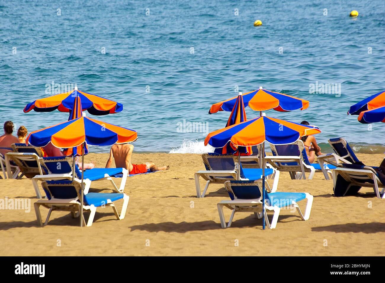 Strandszene mit Liegestühlen und Sonnenschirmen auf der spanischen Kanarischen Isla de Lanzarote und Blick auf den Atlantik. Stockfoto