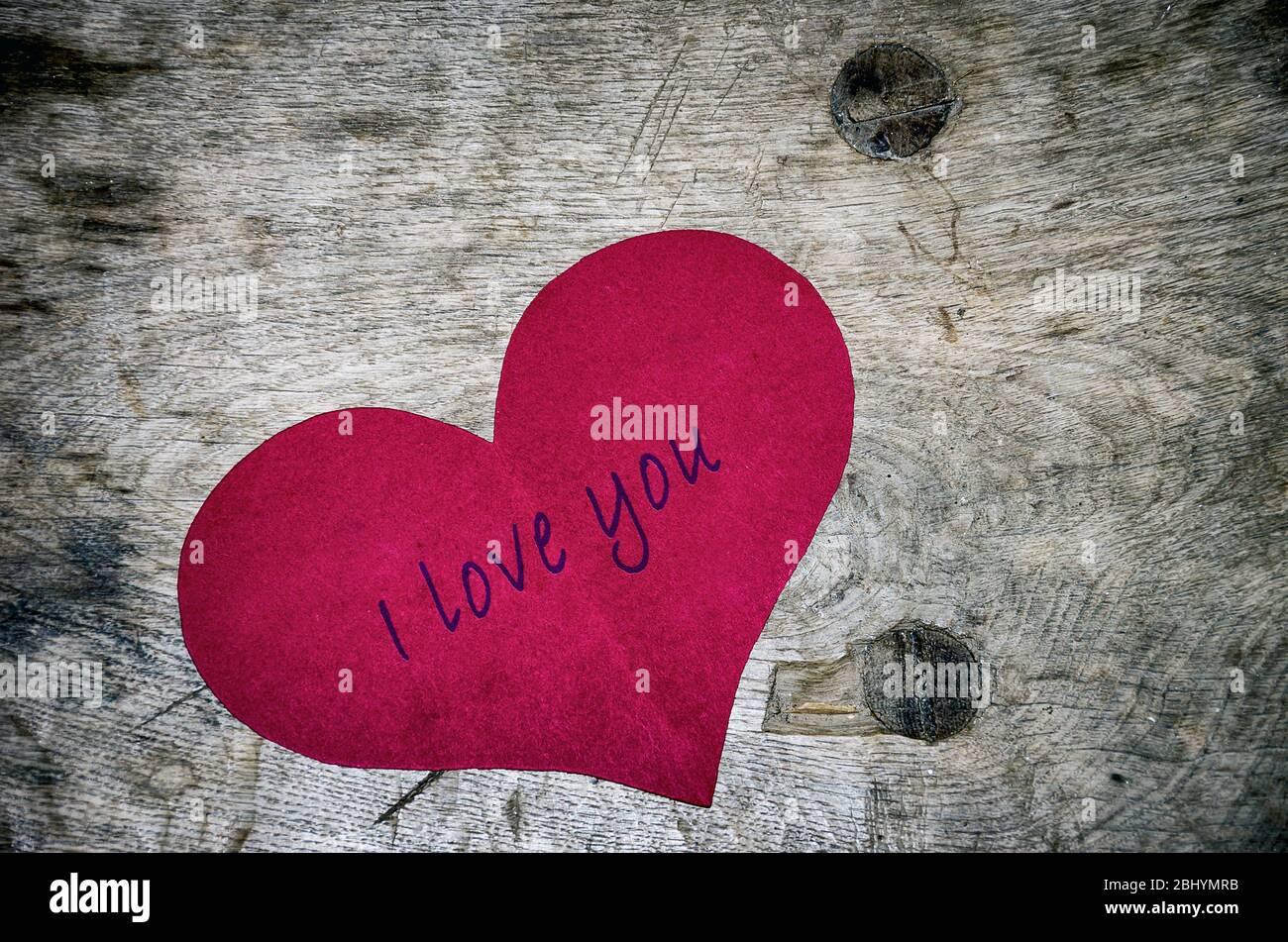 Rotes Papier Herzform auf Holzplatte mit geprägtem Schriftzug Ich LIEBE DICH. Stockfoto