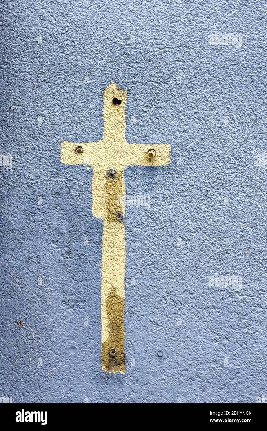 Aufdruck eines Kreuzschildes mit Farbe auf einer Hauswand voller alter Ausdehnungsdübel umgeben. Stockfoto