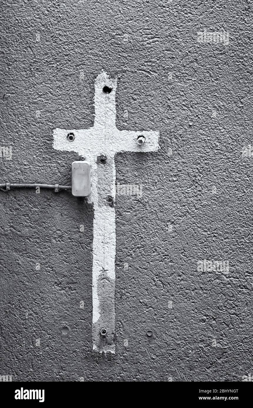 Aufdruck eines mit Farbe umgebenen Kreuzschildes auf einer Hauswand voller alter Ausdehnungsdübel mit Stromanschluss. Stockfoto