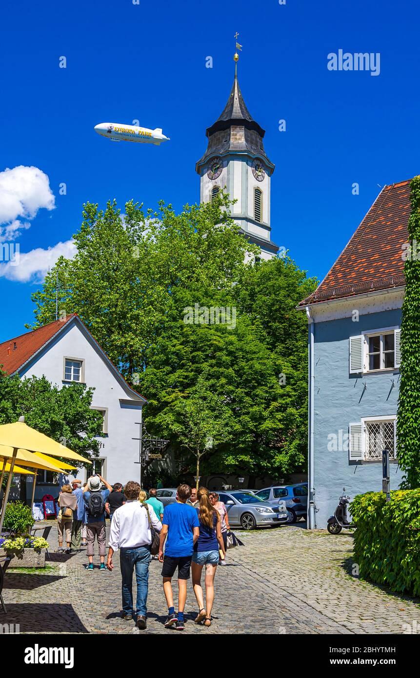 Städtische Szene auf der Lingg-Straße mit Minsterturm und Werbezeppelin über der historischen Altstadt von Lindau im Bodensee, Bayern, Deutschland. Stockfoto