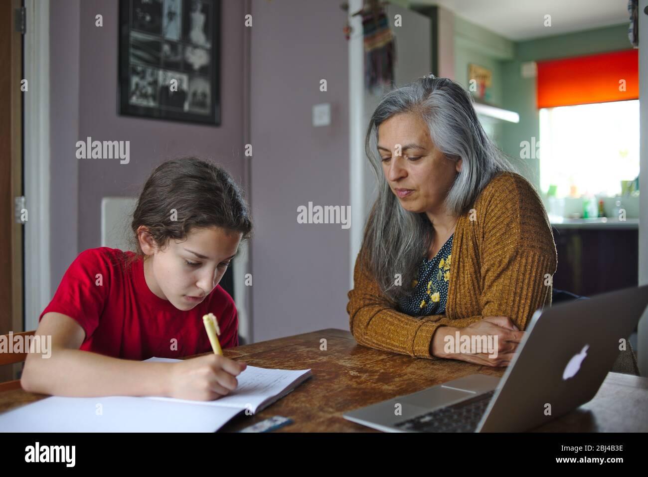 Eltern helfen Kind bei der Schularbeit zu Hause während der Coronavirus-Sperre. April 2020 Großbritannien Stockfoto