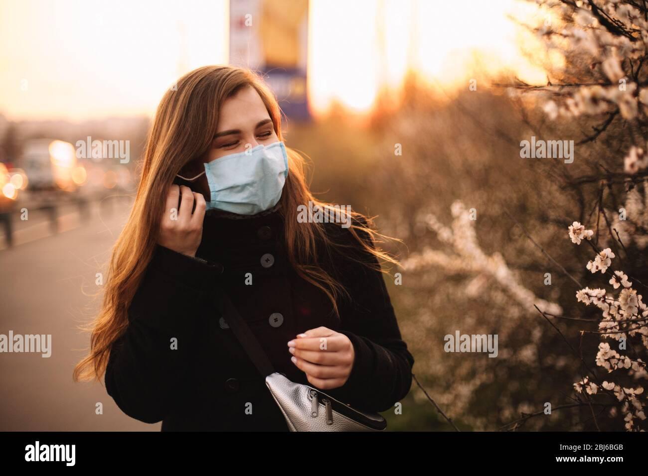 Glückliche junge Frau, die auf Gesicht medizinische Maske während des Stehens auf der Straße in der Stadt während Sonnenuntergang im Frühling setzt Stockfoto