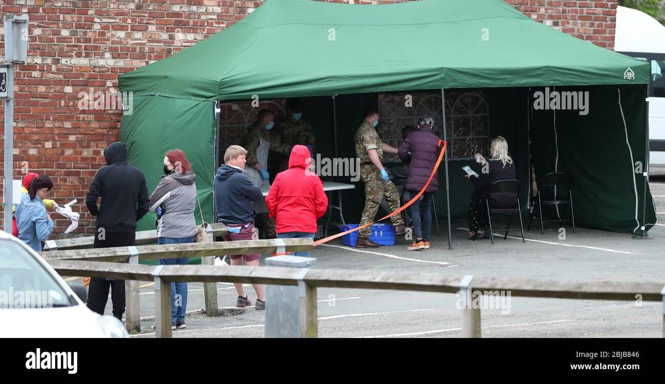 Die Leute stehen in einem begehbaren Coronavirus-Testzentrum an, das von Soldaten des Regiments des Herzogs von Lancaster in Macclesfield, Cheshire, besetzt ist. Stockfoto