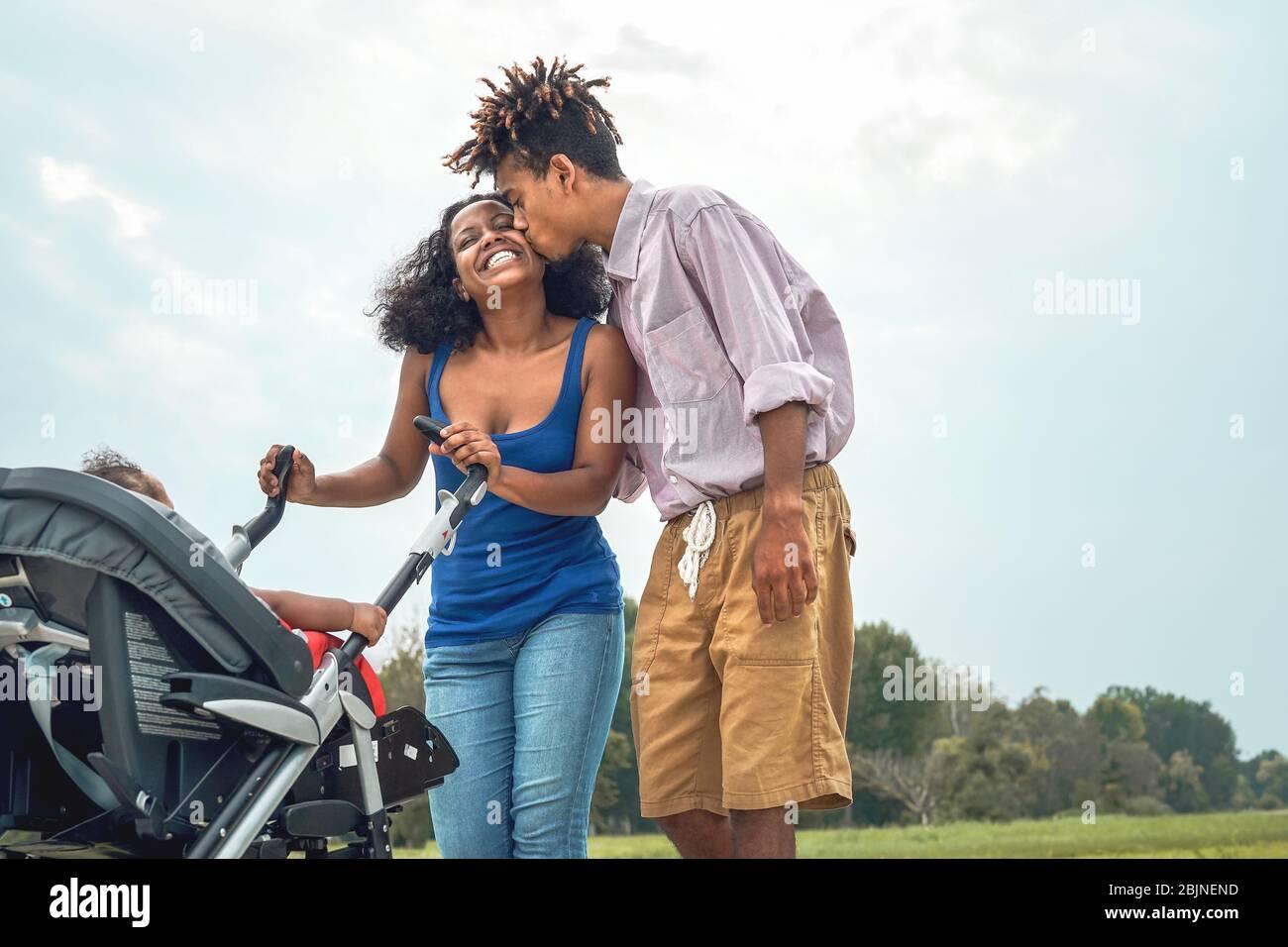 Glückliche afrikanische Familie, die Spaß zusammen im öffentlichen Park hat - Afro Mutter und Vater mit ihrer Tochter, die Zeit zusammen am Wochenende draußen genießen Stockfoto