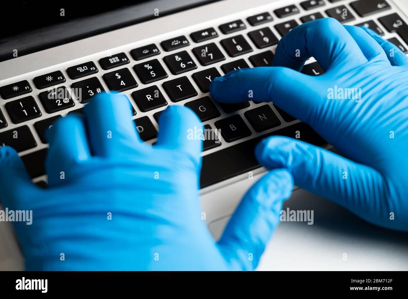Arbeiten mit Schutzhandschuhen an einem Computer. Coronavirus-Prävention. Sicheres Arbeiten im Büro mit Notebook. Stockfoto